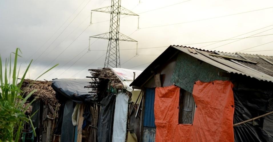 29.abr.2014 - Acampamento Bom Regente, às margens da BR-101 e sob linhas de transmissão de energia de alta tensão, tem casas sem energia