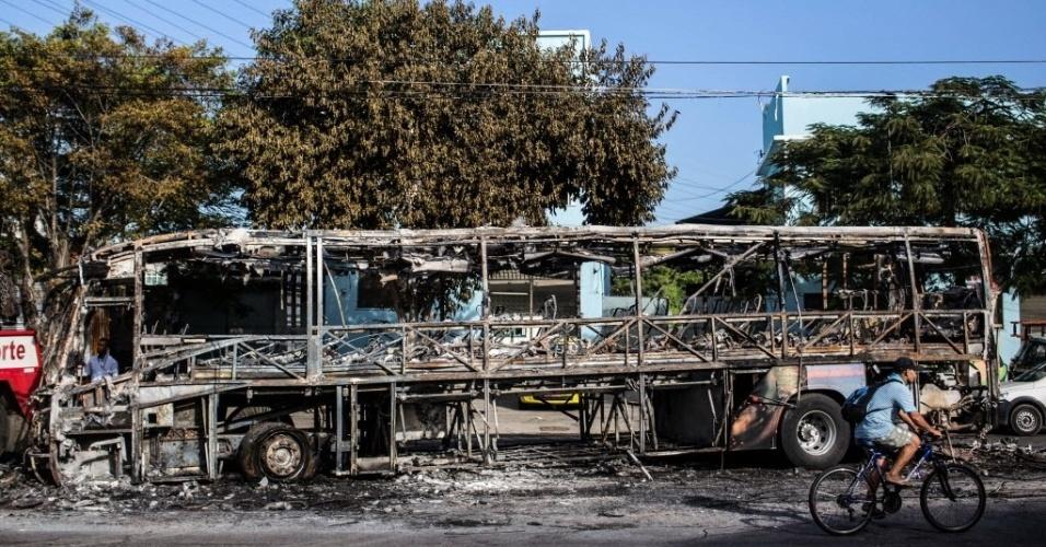 29.abr.2014 - Ciclista passa perto do que restou de um ônibus queimado nesta terça-feira (29), no Rio de Janeiro. Nove veículos do transporte coletivo foram incendiados e uma pessoa foi baleada após uma noite de distúrbios no complexo de favelas do Alemão. Desde o início do ano, 45 ônibus foram destruídos no Estado em incêndios criminosos, informou o Rio Ônibus, sindicato dos quatro consórcios que atuam na cidade do Rio de Janeiro. Do total, 38 ocorreram na capital