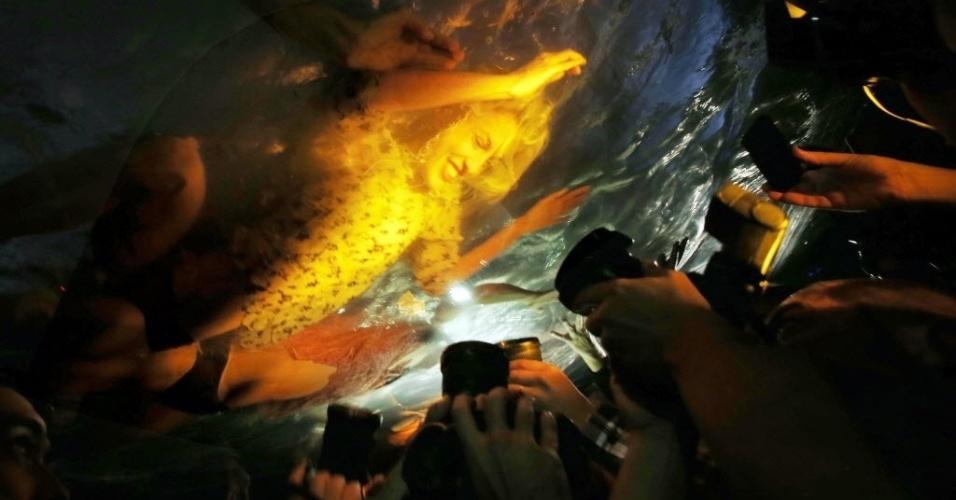 """29.abr.2014 - Fotografia tirada em 28 de abril e divulgada nesta terça-feira (29) mostra uma atriz se movendo dentro de um aquário de plástico enquanto é fotografada durante ensaio do espetáculo """"Força Bruta"""", antes da sua estreia em Santiago, no Chile"""