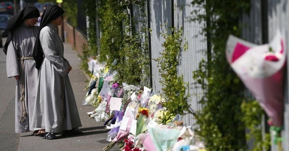 29.abr.2014 - Freiras observam arranjos de flores colocados no chão, em frente à instituição católica de ensino Corpus Christi, em Leeds (Inglaterra), onde a professora Anne Maguire foi esfaqueada. A polícia britânica prendeu um estudante de 15 anos como suspeito do crime