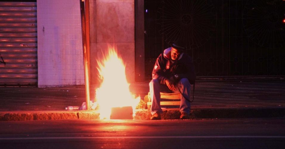 29.abr.2014 - Homem se esquenta ao lado de fogueira no centro de São Paulo, na madrugada desta terça-feira (29). Os termômetros chegaram a registrar 14ºC na capital paulista