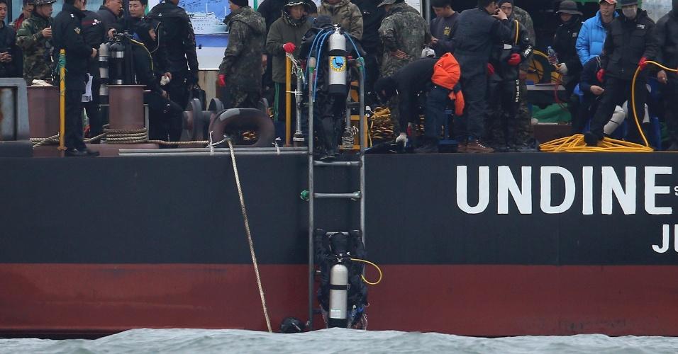 29.abr.2014 - Mergulhadores sul-coreanos sobem a escada de um navio, nesta terça-feira (29), depois de procurar mais vítimas do naufrágio da balsa Sewol. Eles buscam mais de 100 corpos que ainda estão presos na embarcação, submersa 30 metros abaixo da superfície