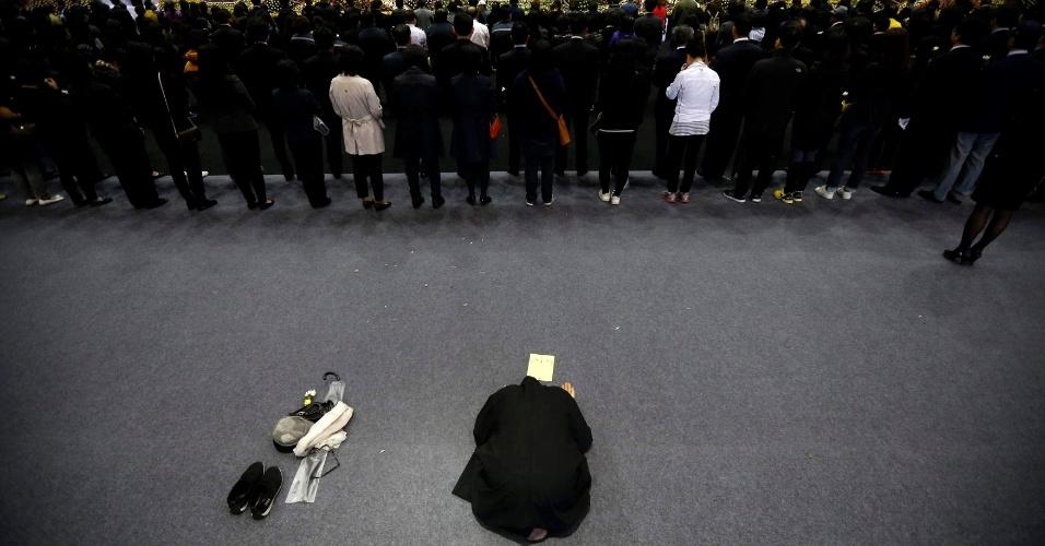29.abr.2014 - Monge budista reza enquanto pessoas aguardam em fila para prestar homenagem às vítimas da balsa Sewol, naufragada no último dia 16, em memorial em Ansan, ao sul de Seul, nesta terça-feira (29). Mais de 300 pessoas, a maioria estudantes e professores de Ensino Médio, morreram ou estão desaparecidos após a tragédia, ocorrida a 20 km da costa no sul da Coreia do Sul