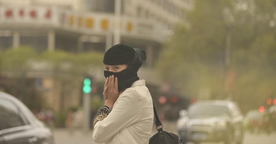 29.abr.2014 - Mulher caminha com o rosto coberto em Xining, capital da província chinesa de Qinghai, cidade que foi tomada por uma nuvem de poeira nesta terça-feira (29)