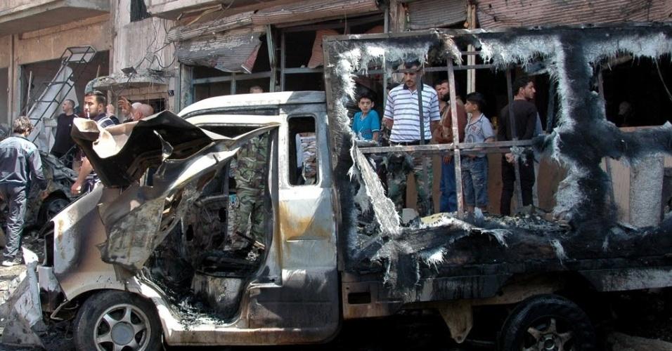 29.abr.2014 - Sírios observam local onde um carro-bomba explodiu nos arredores da cidade de Homs (Síria), nesta terça-feira (29). Segundo informações do governador da província à AFP, a explosão aconteceu em uma área onde estavam muitas pessoas, logo depois de um ataque com foguetes na mesma região