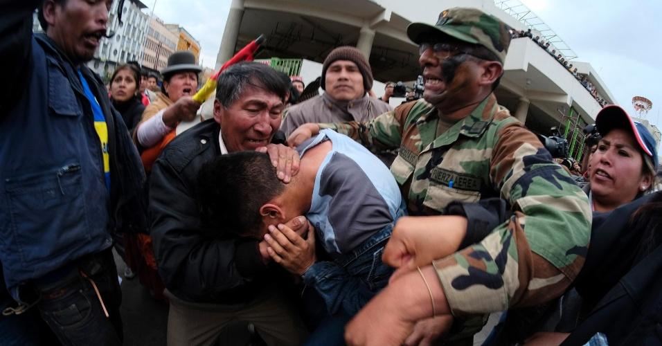 """29.abr.2014 - Um oficial de inteligência que estava infiltrado em um protesto de oficiais do Exército e baixa patente se protege contra os manifestantes na praça de San Francisco, em La Paz, na Bolívia, nesta terça-feira (29). Os oficiais das Forças Armadas protestam contra a demissão de centenas de soldados por """"insubordinação"""", de acordo com a imprensa local"""