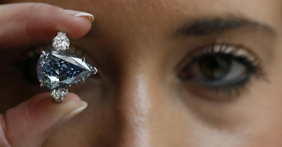"""29.abr.2014 - Uma funcionária segura o diamante """"O Azul"""" na casa de leilões Christie, em Londres, na Inglaterra, nesta terça-feira (29). O estabelecimento está exibindo um dos seus mais extravagantes diamantes, orçado em quase US$ 25 milhões (o equivalente a cerca de R$ 55,9 milhões), e que deve ser um dos destaques na próxima venda da Magnificent Jewels, em Genebra (Suíça)"""