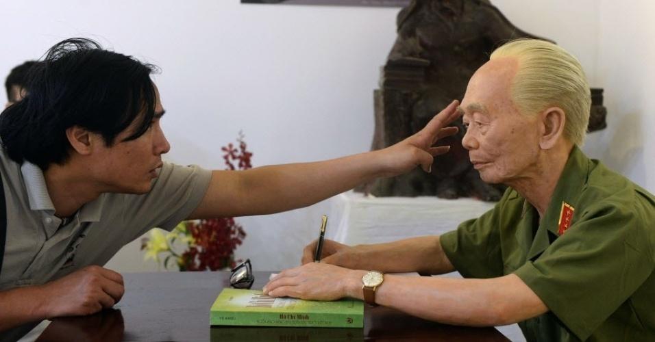 29.abr.2014 - Visitante de um museu sobre o Exército de Hanói (Vietnã) toca o rosto de uma réplica, feita em silicone, em tamanho natural, do general Vo Nguyen Giap, cujas tropas venceram os franceses em 1954, na batalha de Dien Bien Phu. O país vai comemorar 60 anos do evento na semana que vem