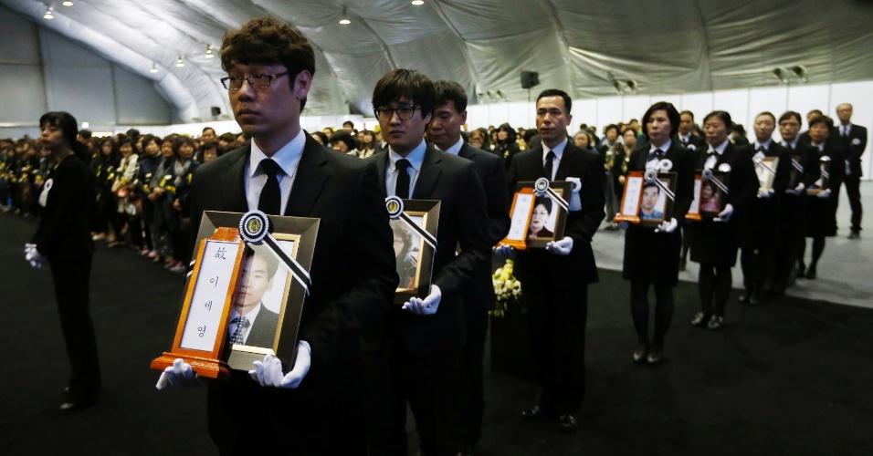 29.abr.21014 - Funcionários de serviços funerários levam retratos das vítimas do naufrágio da balsa Sewol para o altar do memorial oficial, em Ansan, na Coreia, nesta terça-feira (29)