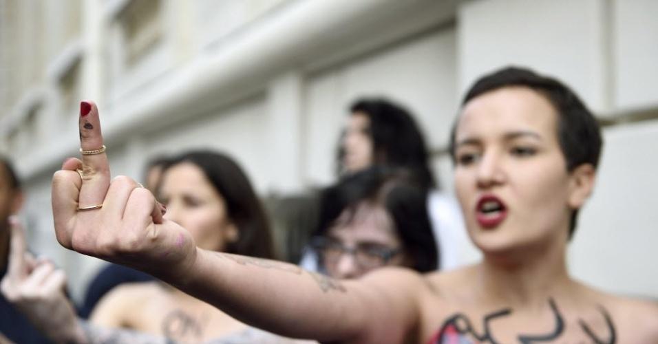 30.abr.2014 - Ex-ativista do Femen da Tunísia, Amina Sboui faz gesto obsceno durante protesto em frente à embaixada do Egito em Paris (França) contra a condenação à morte de 683 islamitas egípcios, acusados de promover distúrbios e mortes em nome do apoio ao presidente deposto Mohammed Mursi. Lê-se, da esquerda para a direita, pintado nos corpos das ativistas do Femen: