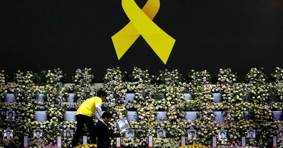 30.abr.2014 - Funcionários colocam foto de vítima da balsa naufragada na costa da Coreia do Sul no altar memorial em Ansan, nesta quarta-feira (30). A balsa Sewol afundou em 16 de abril durante uma viagem de rotina entre Icheon e Juju, no sul do país, levando 476 pessoas a bordo. Na terça-feira, a presidente da Coreia do Sul, Park Geun-hye, pediu desculpas publicamente pela tragédia