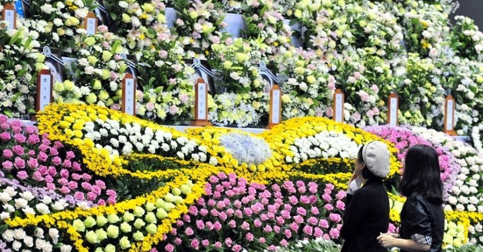 30.abr.2014 - Sul-coreanas fazem suas homenagens aos mortos no naufrágio da balsa Sewol, no dia 16 de abril, no mar ao sul do país. O altar com rosas formando um laço amarelo, simbolizando a esperança, foi montado em Ansan (30 km de Seul), cidade onde estudavam adolescentes que estavam na embarcação, em uma excursão escolar. Das 476 pessoas a bordo, cerca de 300 morreram ou continuam desaparecidas. Ainda não há uma conclusão sobre o que levou a balsa a afundar, mas o capitão foi preso por abandoná-la antes do socorro a todos os passageiros