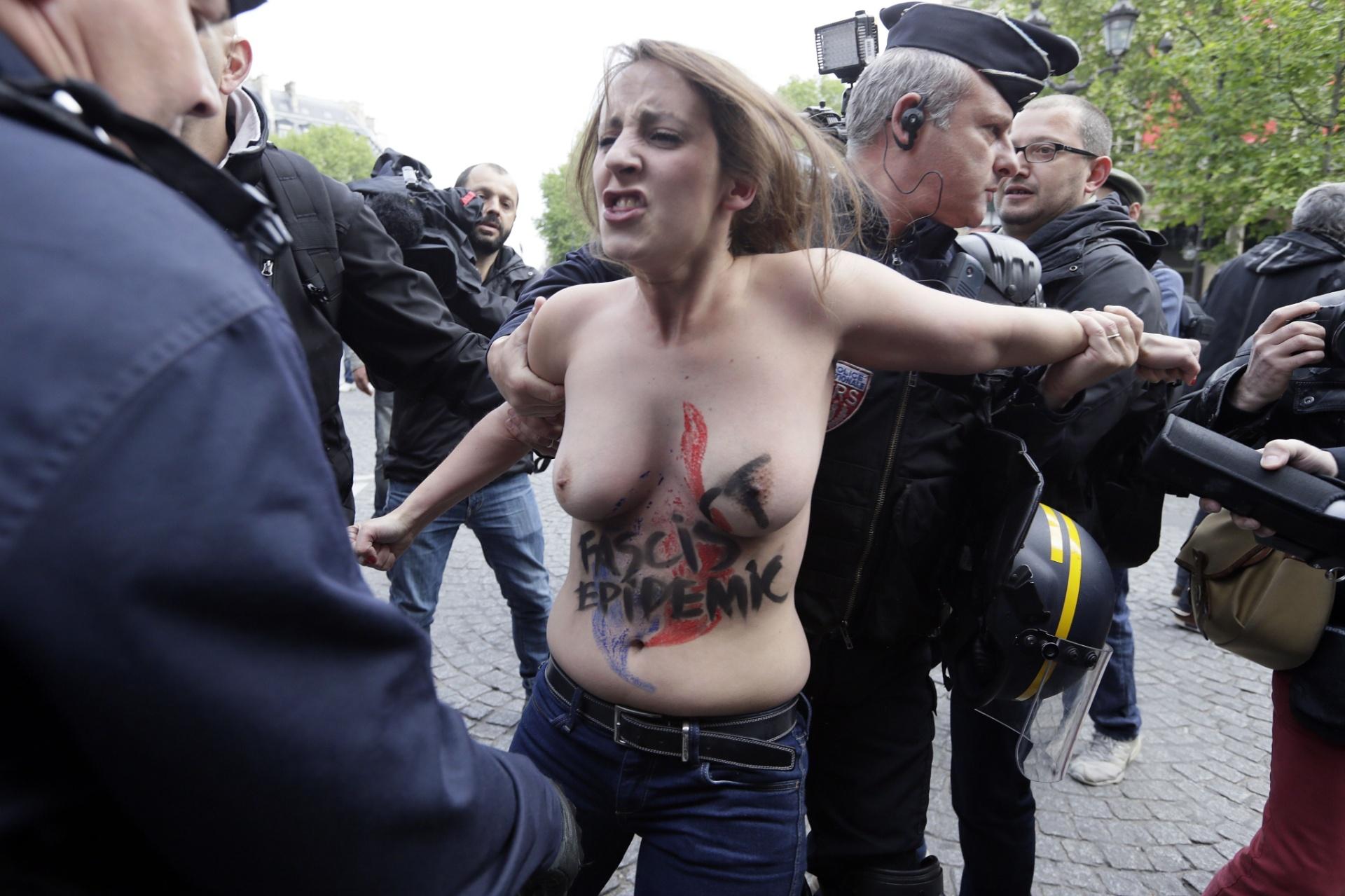 1º.mai.2014 - Policiais franceses detêm manifestante do grupo Femen com o slogan