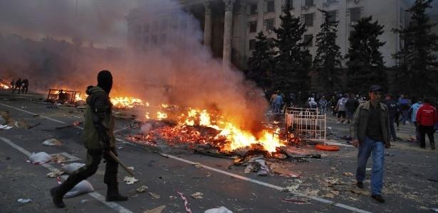 Manifestante passa por um acampamento pró-Rússia em chamas perto do prédio em Odessa