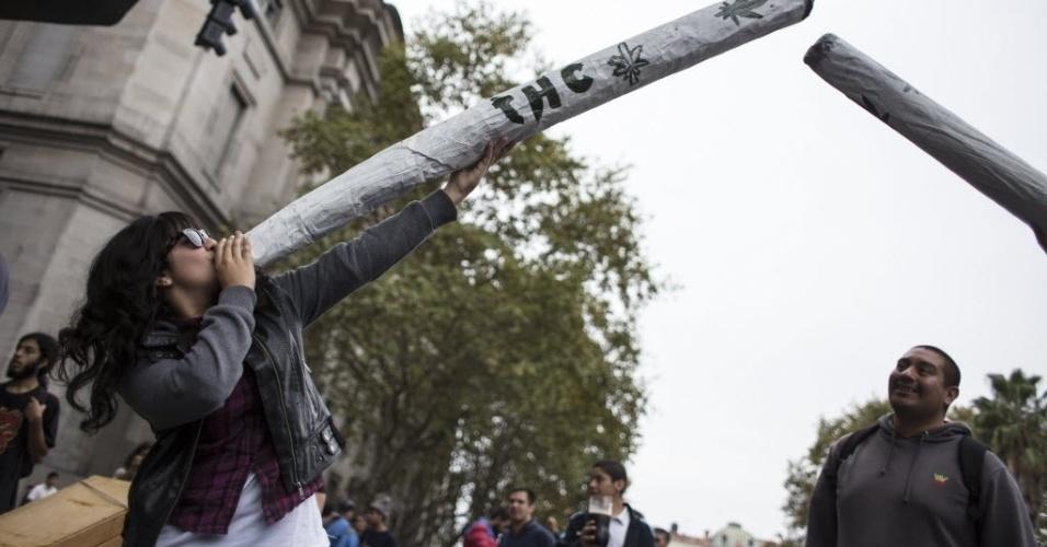 3.mai.2014 - Jovem simula estar fumando cigarro gigante de maconha durante a Marcha Mundial da Maconha em Buenos Aires, capital da Argentina, neste sábado (3). Desde 1999, a marcha mundial é realizada simultaneamente em várias cidades do mundo no primeiro sábado de maio