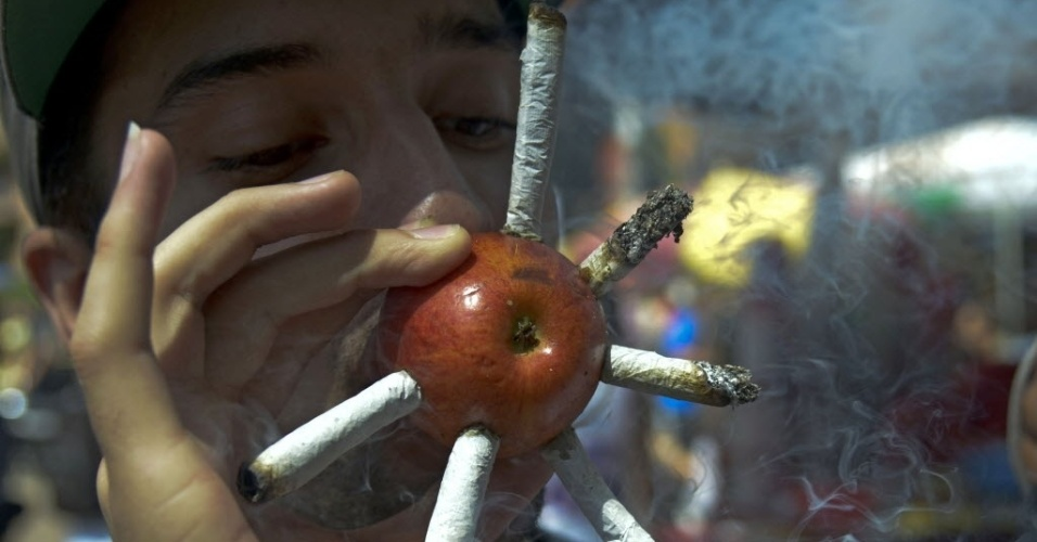 3.mai.2014 - Jovem usa maçã para fumar vários cigarros de maconha durante a Marcha da Maconha em Medellín, na Colômbia. O ato, que acontece simultaneamente em várias cidades do mundo, pede a descriminalização da droga