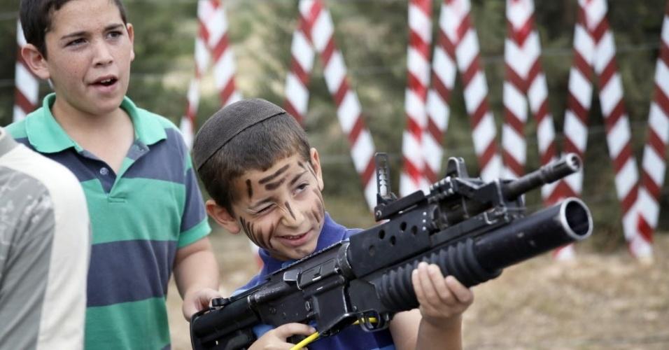 6.mai.2014 - Menino israelense brinca com um rifle M-16 durante uma exibição para marcar o 66º aniversário da independência de Israel, no assentamento de Efrat, na Cisjordânia