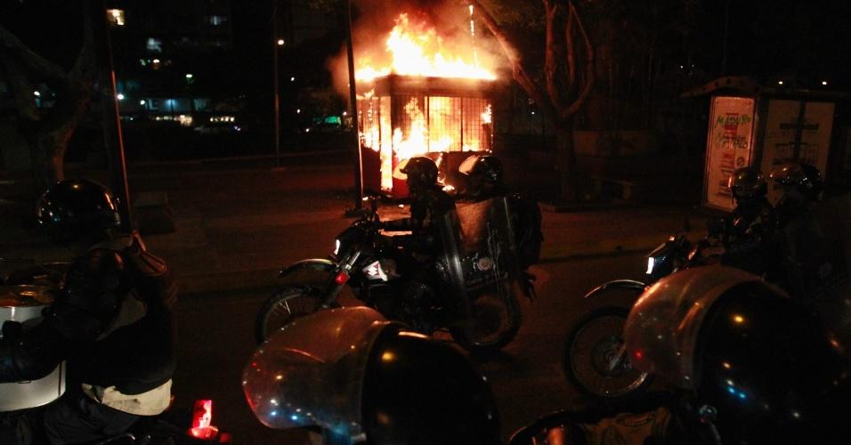 6.mai.2014 - Policias passam por um quiosque em chamas após ser incendiado pro manifestantes próximo a praça Altimara, em Caracas, na Venezuela, nesta terça-feira (6)