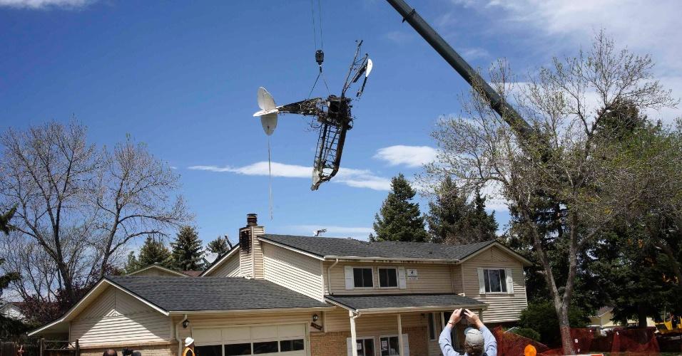 6.mai.2014 - Um guindaste levanta os destroços de um pequeno avião que caiu em uma casa em Northglenn, no Colorado (EUA), nesta terça-feira (6). O piloto de um avião monomotor se agarrou a um banner publicitário e saiu ileso do acidente, após o veículo cair em uma casa desocupada no subúrbio de Denver. A queda causou incêndio no imóvel