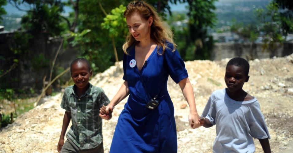 6.mai.2014 - Valerie Trierweiler, ex-mulher do presidente da França, François Hollande, caminha de mãos dadas com dois garotos após visitar o local de construção de estação de água potável, em Joute Bois, Carrefour, em Porto Príncipe, no Haiti, nesta terça-feira (6)