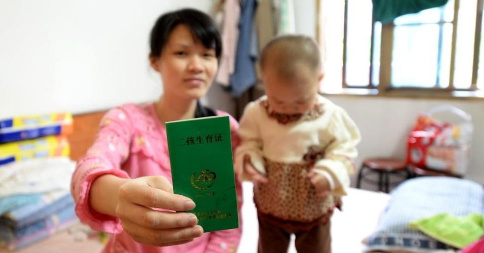 6.mai.2014 - Wei exibe certificado que a autorizou a ter um segundo filho, em Guangxi Zhuang, na China. Nos últimos anos, o governo da China vem flexibilizando a lei que permite apenas um filho por família