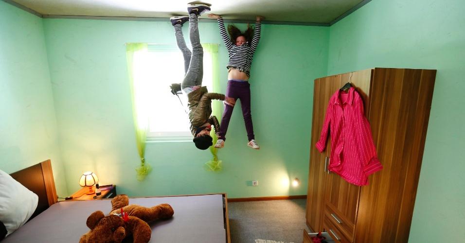 7.mai.2014 - Jovens brincam no quarto da Casa Louca, completamente construída de cabeça para baixo, no vilarejo de Affoldern, perto do lago Edersee, na Alemanha. Três amigos tiveram a ideia de construir uma atração turística no local, que custou 200 mil euros (equivalente a cerca de R$ 620,8 mil) e levou seis semanas para ser erguida