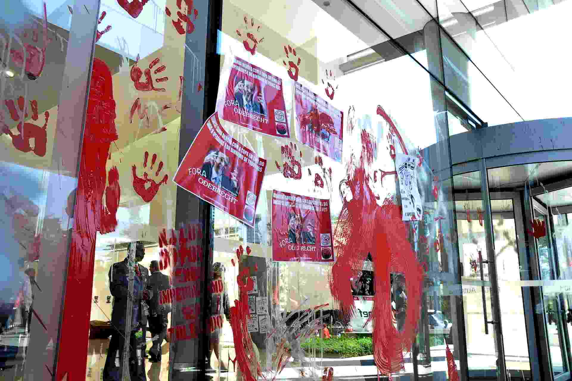8.mai.2014 - Manifestantes atiram tinta em vidro do hall de entrada do escritório da construtora Odebrecht, na marginal Pinheiros, zona oeste de São Paulo, na manhã desta quinta-feira (8). Cerca de 100 integrantes do MST (Movimento dos Trabalhadores Sem Terra) participaram de protesto na capital paulista contra os gastos da Copa do Mundo - Kevin David/Futura Press/Estadão Conteúdo