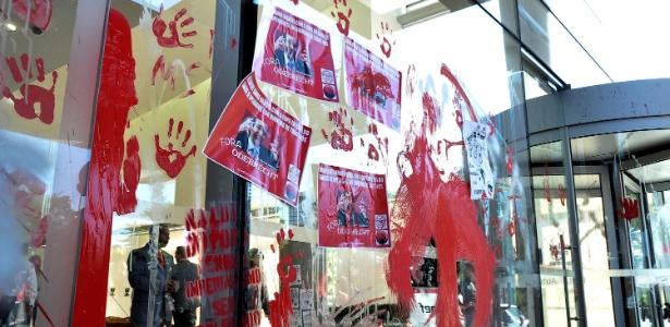 Manifestantes atiram tinta em vidro do hall de entrada do escritório da construtora Odebrecht, em SP