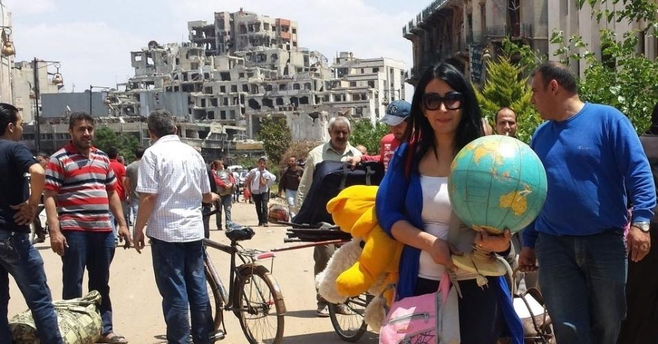 10.mai.2014 - Sírios transportam pertences perto da área de Souk Maskouf na Cidade Velha de Homs, na Síria. Centenas de civis sírios retornaram neste sábado a região. Na sexta-feira, o Exército entrou pela primeira vez em dois anos na área antiga da cidade, após a retirada dos rebeldes por um acordo assinado entre as partes. Muitos civis encontraram suas casa destruídas pelo conflito