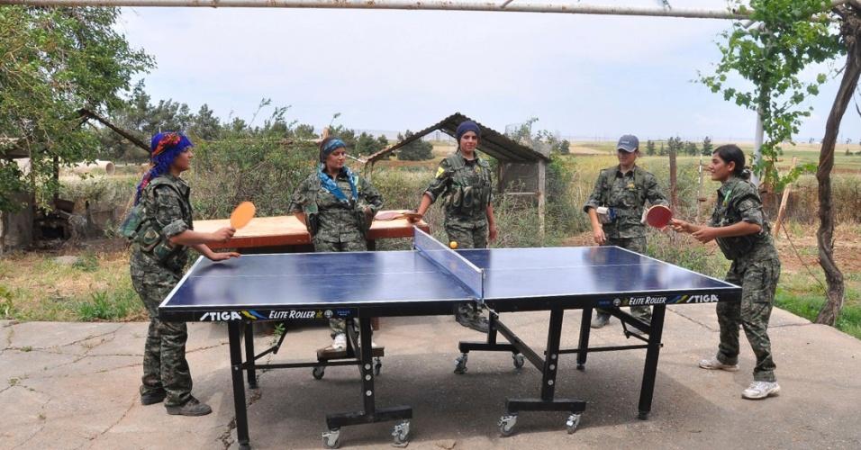 12.mai.2014 - Milicianas curdas da Unidade de Proteção Feminina jogam tênis de mesa em campo de treinamento próximo a Qamishli, na Síria. A imagem, de domingo (11), foi divulgada nesta segunda