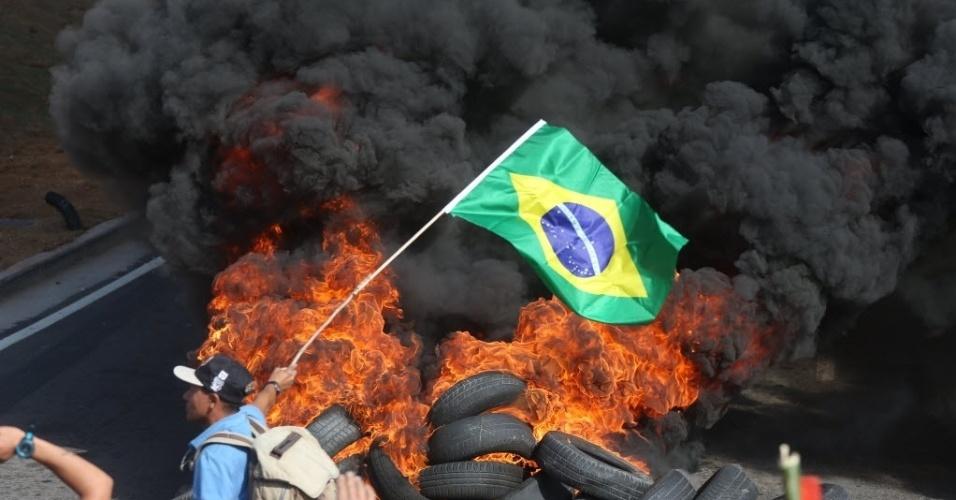 15.mai.2014 - Integrantes do Movimento dos Trabalhadores Sem Teto (MTST) colocam fogo em pneus durante marcha na zona leste de São Paulo, rumo a Arena Corinthians. Protestos organizados por movimentos sociais e grupos contrários à realização da Copa do Mundo estão programados para esta quinta-feira em ao menos 50 cidades do país
