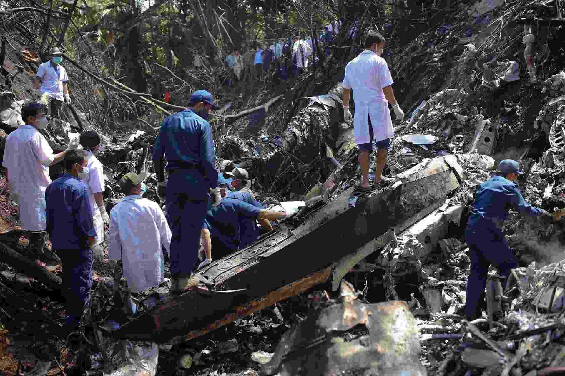17.mai.2014 - Equipes de resgate examinam local em que um avião da Força Aérea do Laos caiu perto da aldeia Nadee, na província de Xiang Khouang, norte do país - Reuters