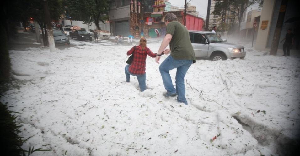 18.mai.2014 - Casal tenta atravessar rua coberta por gelo no bairro da Aclimação, região central de São Paulo. Após 32 dias sem registrar chuva significativa, a capital paulista teve pancadas fortes na tarde de domingo