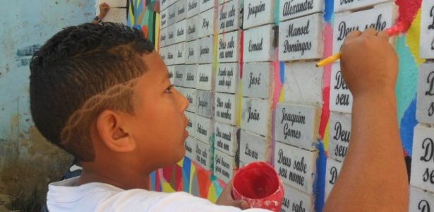 Aluno pinta o painel com os nomes dos 200 escravos que pertenciam ao mesmo dono de Manuel Congo, protagonista da Revolta de Vassouras