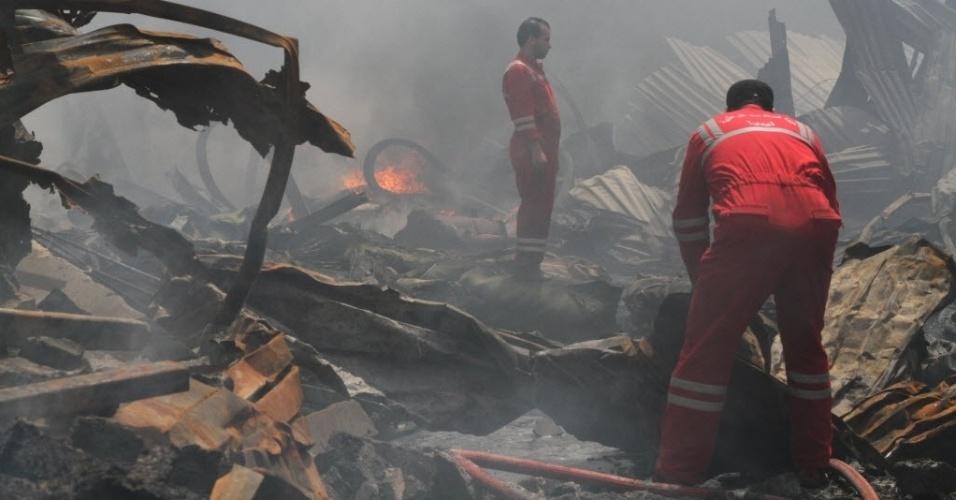 21.mai.2014 - Bombeiros combatem incêndio em local de explosão em Salaheddin, distrito de Trípoli, na Líbia, nesta quarta-feira (21). Pelo menos duas pessoas foram mortas quando pesados combates irromperam perto da capital líbia dois dias depois de homens armados terem atacado o Parlamento. Este é um dos momentos de maior violência desde a guerra civil que culminou com a queda do ditador Muammar Gaddafi