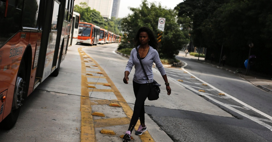 21.mai.2014 - Uma pedestre caminha ao lado de fila de ônibus parados na avenida Rebouças, na zona oeste de São Paulo, durante paralisação dos motoristas e cobradores de ônibus, nesta quarta-feira (21). Parte da categoria está parada há dois dias e afirma que optou por estacionar os ônibus nas ruas para evitar retaliações do próprio sindicato e das empresas. O Sindimotoristas, que representa a categoria, havia ordenado que os veículos deixassem as garagens e circulassem normalmente