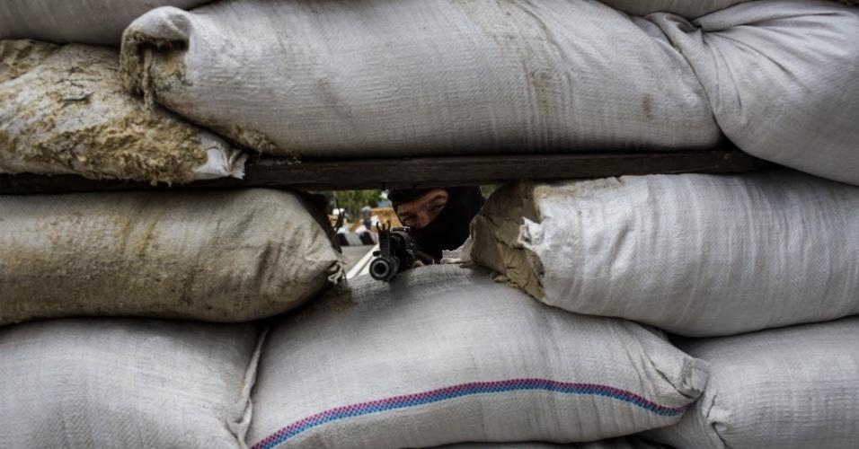 23.mai.2014 - Atirador de força separatista pró-Rússia aponta arma atrás de barricada em Pisky, a 15 km de Donetsk, no leste da Ucrânia. Os combates, que ocorrem dois dias antes das eleições presidenciais, deixaram pelo menos duas pessoas mortas, de acordo com testemunhas