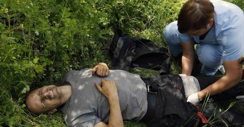 23.mai.2014 - Médicos prestam primeiros-socorros a homem ferido durante confronto na região rural de Karlovka, no oeste de Donetsk, na Ucrânia. Separatistas russos abriram fogo contra milícias pró-Ucrânia. Ao menos duas pessoas morreram, segundo testemunhas