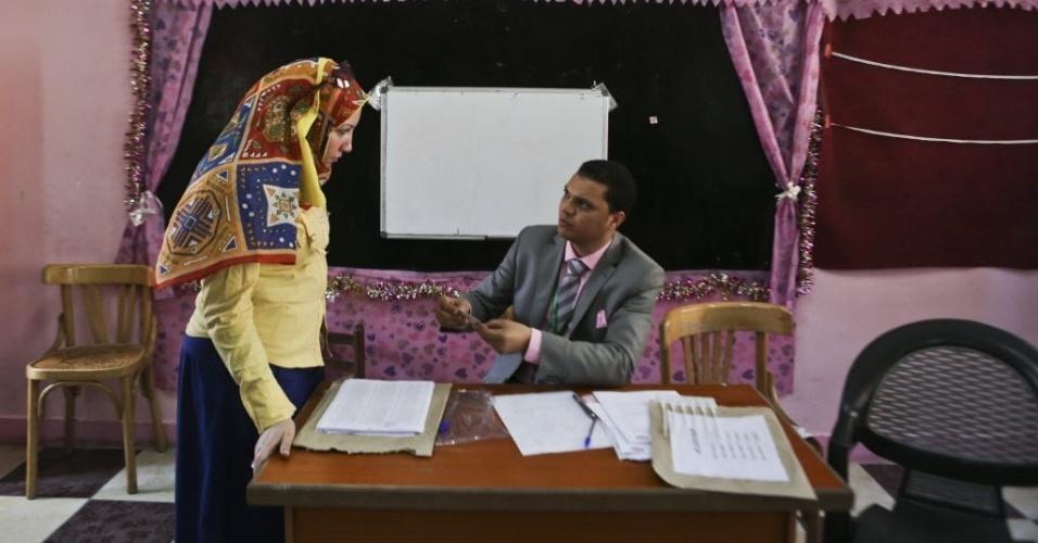 26.mai.2014 - Mulher conversa com oficial em sessão eleitoral antes de votar em eleições presidenciais do Egito. Votam nesta segunda e terça-feira 53 milhões de eleitores. Seus resultados serão anunciados no dia 5 de junho e, posteriormente, serão convocadas eleições legislativas