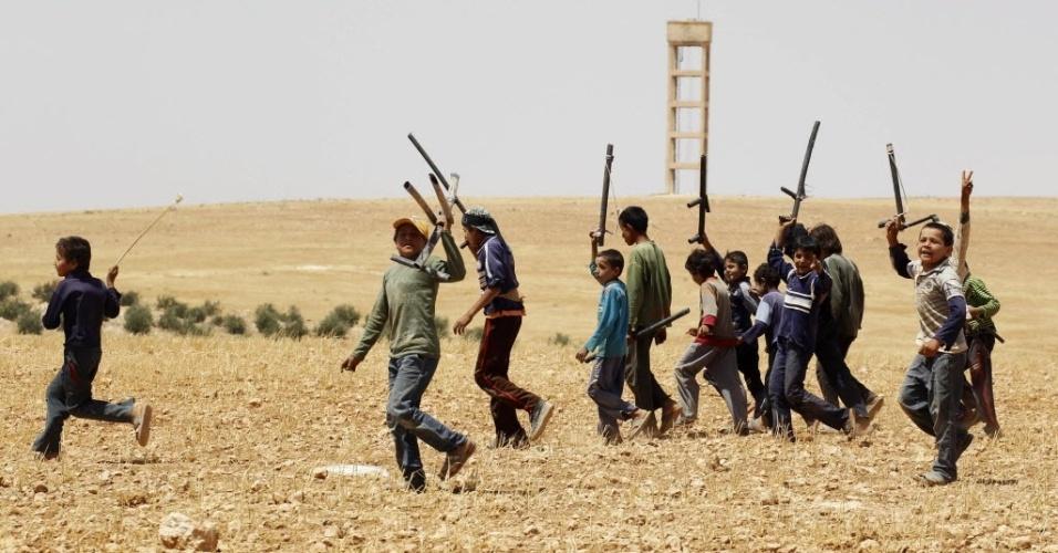 29.mai.2014 - Crianças sírias cantam com armas falsas feitas com tubos durante treinamento com estilo semelhante a 'militar' em área rural de Hama, no oeste da Síria, em foto tirada na quarta-feira (28) e divulgada nesta quinta-feira. A maioria dos meninos tem parentes no Exército Livre da Síria (ELS) e formou sua própria