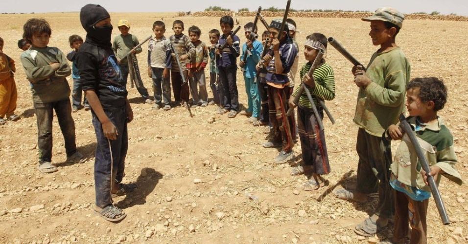 29.mai.2014 - Crianças sírias carregam armas falsas feitas com canos durante treinamento com estilo semelhante ao 'militar' em área rural de Hama, no oeste da Síria, em foto tirada na quarta-feira (28) e divulgada nesta quinta-feira. A maioria dos meninos tem parentes no Exército Livre da Síria (ELS) e formou sua própria