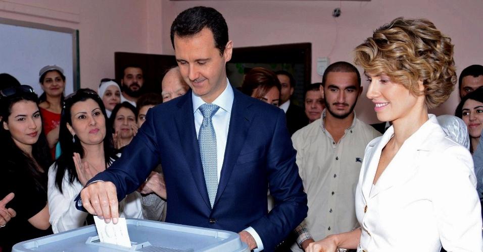 3.jun.2014 - Bashar al-Assad, ditador da Síria, vota, ao lado da mulher, Asma al-Assad, em Maliki, no centro de Damasco, nas eleições presidenciais do país, nesta terça-feira (3). Espera-se que a eleição resulte em uma vitória esmagadora, no que a opinião internacional considera uma farsa para legitimar sua posição na presidência, que ocupa desde 2000