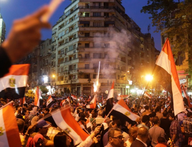 3.jun.2014 - Egípcios erguem bandeiras nacionais após divulgação da vitória do ex-chefe do Exército Abdel Fattah al-Sissi nas eleições presidenciais, na praça Tahrir