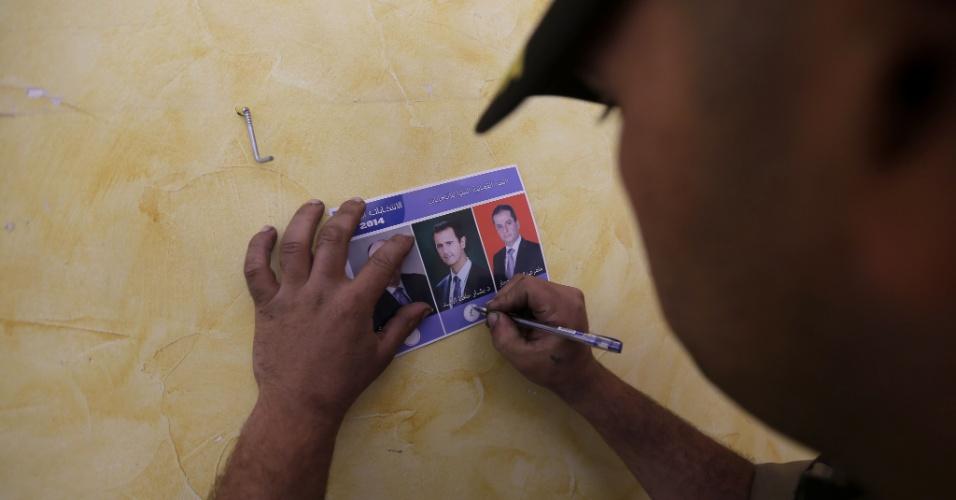 3.jun.2014 - Eleitor assinala a foto de Bashar al-Assad, atual presidente sírio e candidato a reeleição, em cédula de votação na igreja Umm al-Zunnar, em Homs