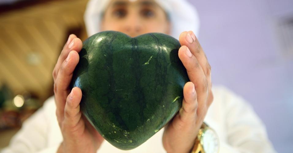 3.jun.2014 - Homem exibe uma melancia em forma de coração em um dos principais supermercados do  Kuait, nesta terça-feira (3). A fruta rara, que é importada do Japão, é vendida por 99 dinares do Kuait, o que representa aproximadamente US $ 350