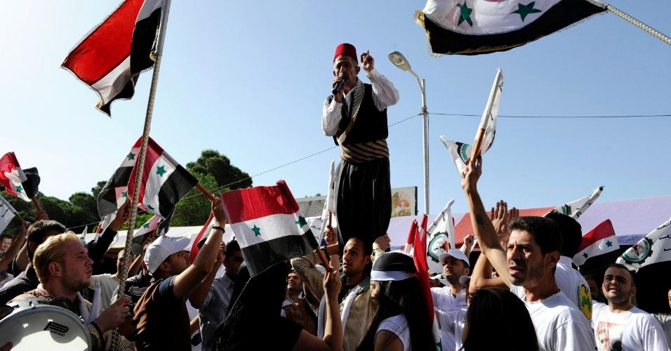 3.jun.2014 - Partidários do ditador sírio Bashar al-Assad acenam bandeiras nacionais e discursam em frente à sede da Federação Geral dos Sindicatos, em Damasco, ao início das eleições na Síria, nesta terça-feira (3). A votação começa, em meio à guerra civil que já matou mais de 160.000 pessoas, vista com muita desconfiança. Assad concorre com outros dois candidatos desconhecidos da população, e as potências ocidentais consideram o pleito uma farsa, que tem por meta legitimar o poder que Assad herdou do pai, Hafez, em 2000