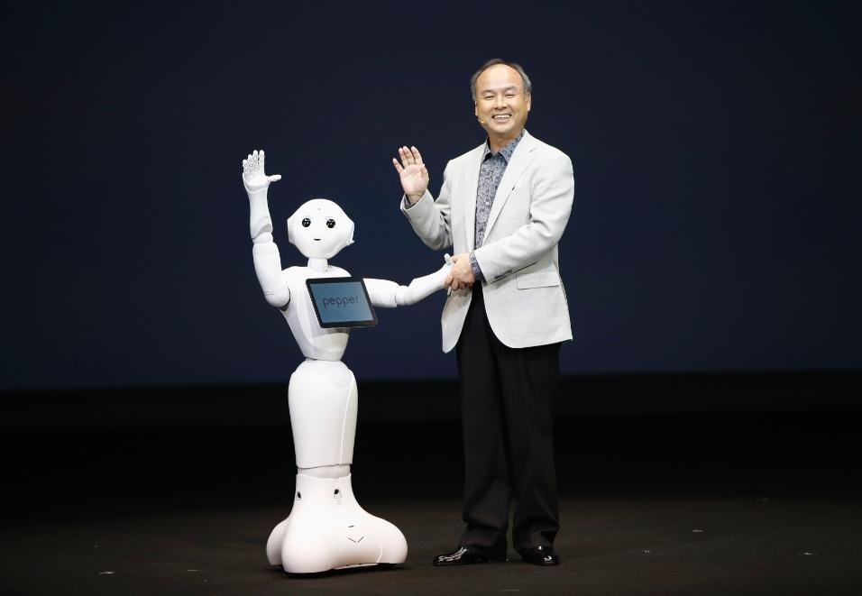 5.jun.2014 - Masayoshi Son, diretor-executivo da operadora japonesa Softbank, posa ao lado do robô humanóide Pepper durante coletiva de imprensa em Tóquio (Japão). Segundo o executivo, a Softbank tem desenvolvido robôs para ajudarem no atendimento nas lojas de celular da companhia. O robô tem 1,21 m e consegue reconhecer reações humanas com a ajuda de câmeras. Feito em parceria com a Aldeberan (empresa francesa que desenvolve robôs), o pepper vai começar a ser vendido em fevereiro de 2015 e o preço sugerido por ele é de 198 mil ienes (cerca de R$ 4.400)