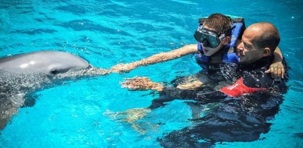 O treinador cubano Adrián Calderón ajuda o menino Javier Gonzalez a tocar um golfinho, durante sessão de terapia no Aquário Nacional de Cuba