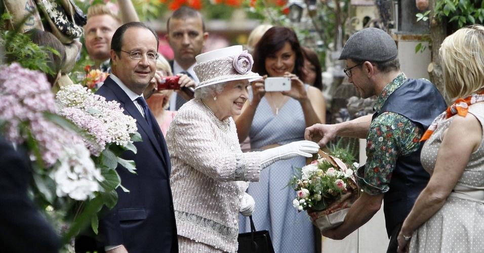 7.jun.2014 - A rainha britânica Elizabeth 2º recebe uma cesta de flores ao lado do presidente da França, François Hollande, durante visita ao Mercado de Flores em Paris, neste sábado (7). A rainha termina a sua visita de três dias à França, por ocasião das cerimônias alusivas ao Dia D, que marcaram os 70 anos do desembarque de tropas na Normandia, durante a Segunda Guerra Mundial, um dos episódios decisivos para o fim do confronto