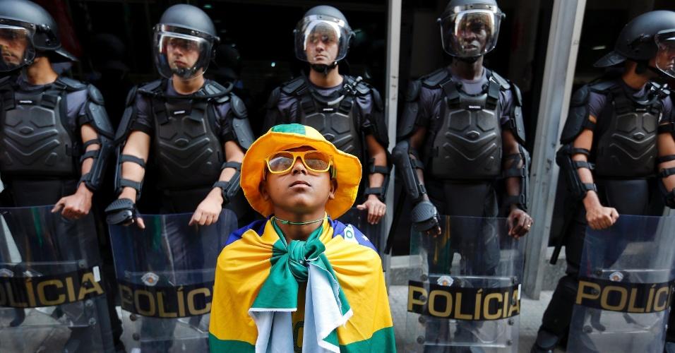 9.jun.2014 - Garoto com a bandeira do Brasil posa para a foto diante de grupo de policiais que reforça a segurança na sede da Secretaria dos Transportes Metropolitanos, na região central de São Paulo, na manhã desta segunda-feira. Um grupo de manifestantes seguiu para o local para demonstrar apoio à greve dos metroviários, que chega ao quinto dia consecutivo nesta segunda-feira